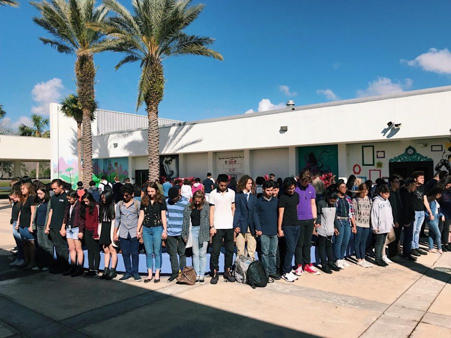 OCSA students hold hands and bow their hands during 17 minute walkout.
