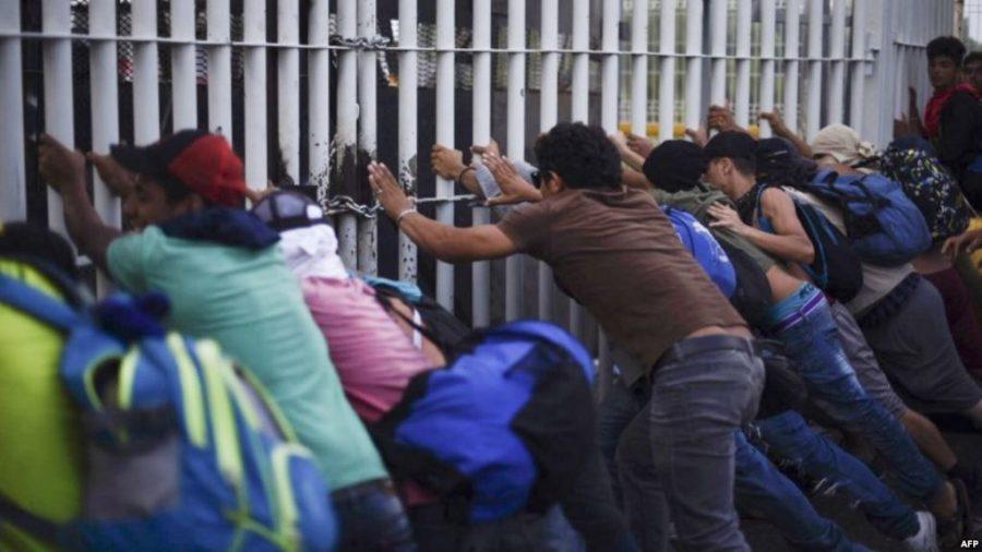 Honduran migrants in a caravan heading to the US, destroy the border fence between Ciudad Tecun Uman in Guatemala and Ciudad Hidalgo, Mexico, Oct. 28, 2018. (VOANEWS)