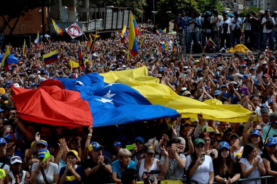 Participants in a mass opposition rally against Venezuelan leader Nicolás Maduro on Wednesday in Caracas listen to National Assembly head Juan Guaidó, who declared himself the rightful president of Venezuela.