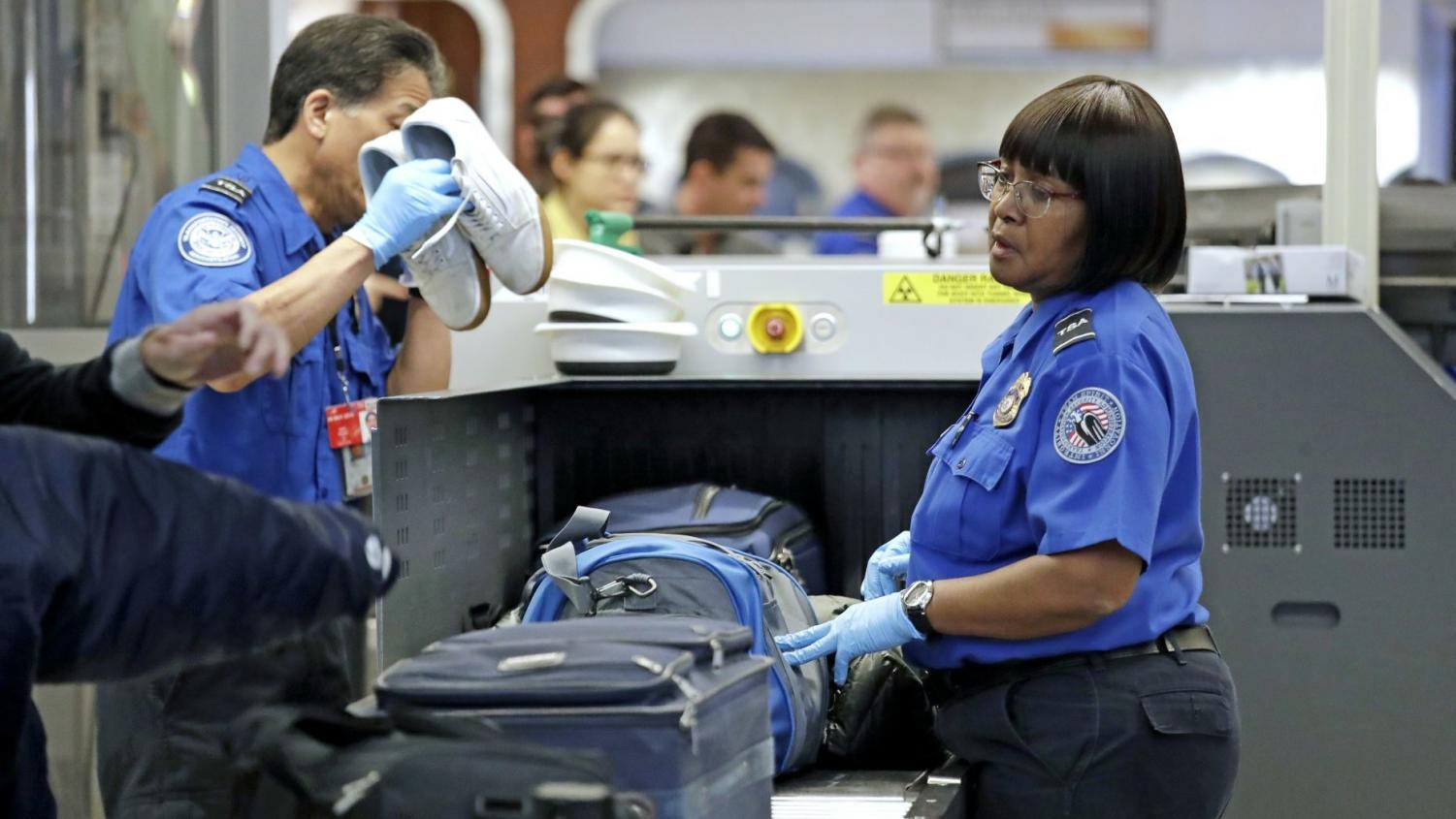 TSA officers screen luggage during partial government shutdown December 31,2018 at Seattle-Tacoma International Airport in Washington.