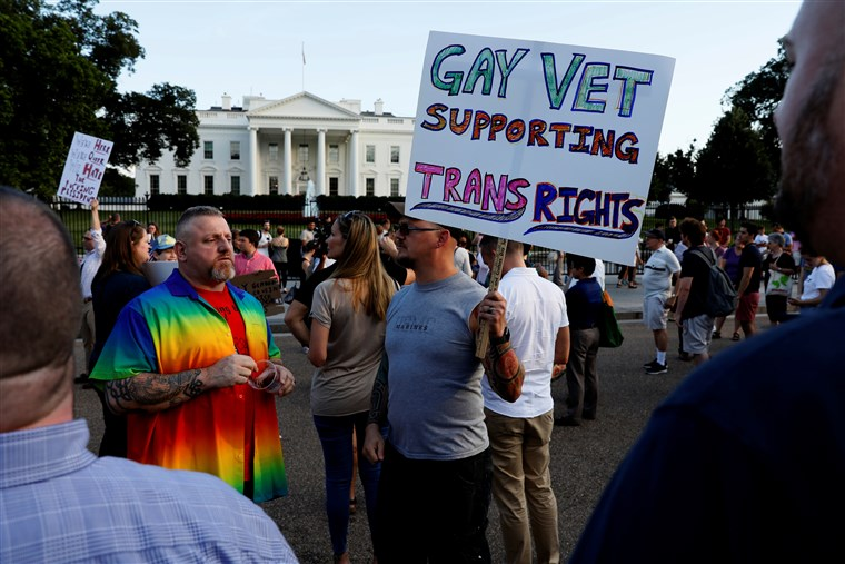Demonstrators gather to protest President Donald Trump's announcement that he plans to reinstate a ban on transgender individuals from serving in any capacity in the U.S. military, at the White House on July 26, 2017