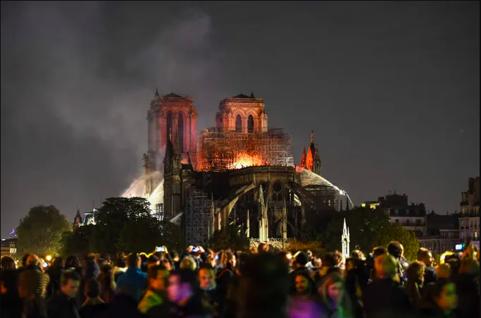 People of France stand and watch as their beloved cathedral, Notre-Dame, burns silently through the night.
