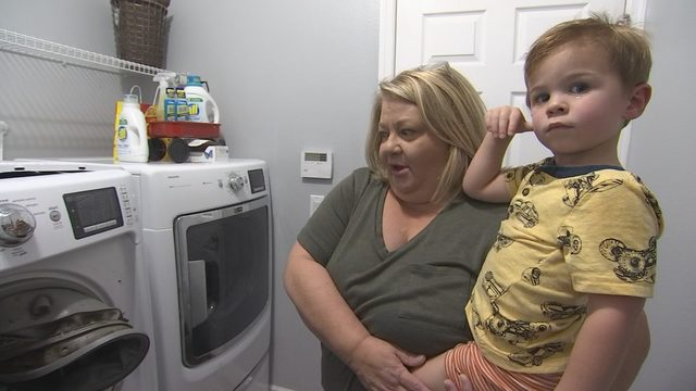Thelma Chattey and her grandson next to their broken washer.