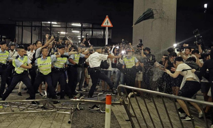 Police officers use pepper spray against protesters in Hong Kong. Photograph: Vincent Yu/AP