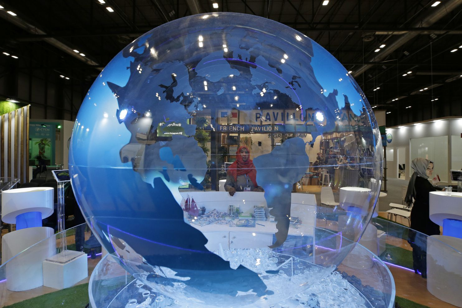 A woman looks at a World globe at the United Nations climate talks in Madrid, Spain, on Friday. Officials from almost 200 countries met for two weeks to work on policy recommendations to deal with the climate crisis. Several issues have been pushed to the next climate conference in November 2020.