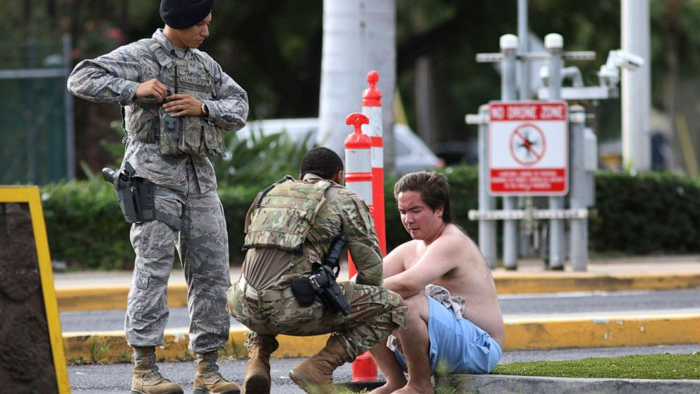 Security forces attend to an unidentified male outside the the main gate at Joint Base Pearl Harbor-Hickam, Wednesday, Dec. 4, 2019, in Hawaii, following a shooting.