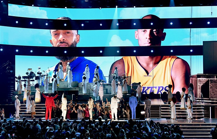 Images of the late Nipsey Hussle and Kobe Bryant are projected onto a screen while YG, John Legend, Kirk Franklin, DJ Khaled, Meek Mill and Roddy Ricch perform during the Grammy Awards at the Staples Center in Los Angeles on Sunday.