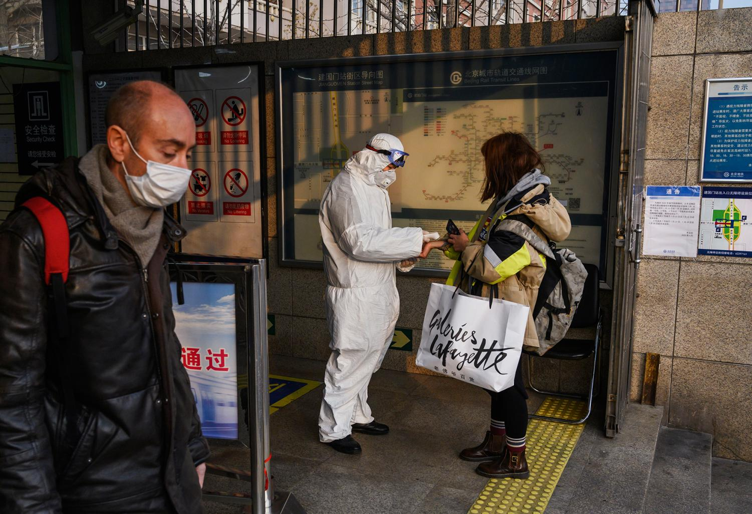 A Chinese worker is dressed in a protective suit as he takes the temperature of a woman at a subway station during the Chinese New Year and Spring Festival holiday on January 28 in Beijing.