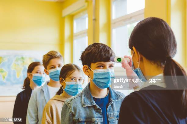 A teacher checks temperature of students at school.  High school students wearing N95 Face masks waiting in line.
