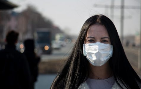 A young woman standing in front of a road, wearing a mask, which is one of the factors to avoiding the coronavirus.
