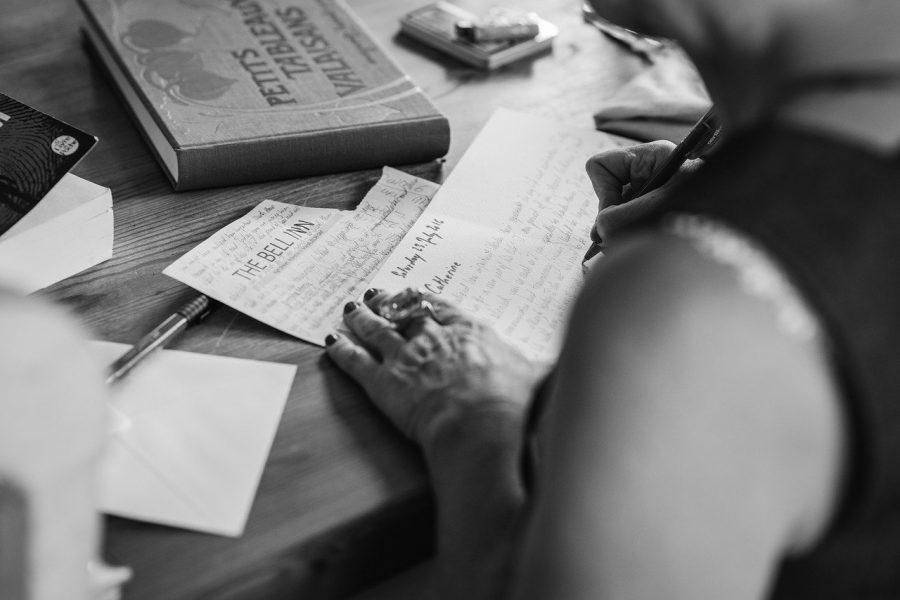 Black and white photo of someone writing.