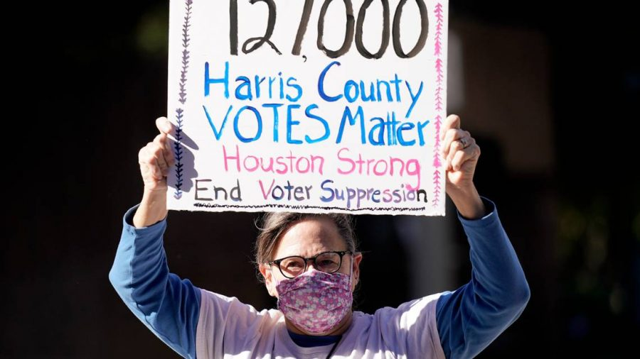 Demonstrator Gina Dusterhoft holds up a sign as she walks to join others standing across the street from the federal courthouse in Houston on Monday, Nov. 2, 2020, before a hearing in federal court involving drive-thru ballots cast in Harris County.