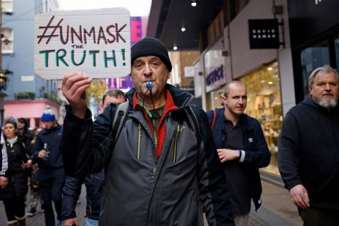 A protester holds up a placard as he takes part in an anti-lockdown protest against government restrictions in London on Saturday.