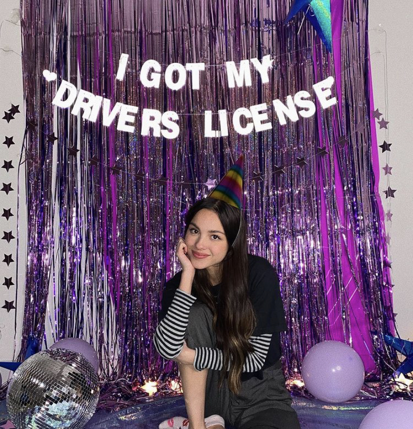 "Olivia Rodrigo poses under a string of letters that read ""I got my Drivers License."" (Rodrigo's Instagram page)"