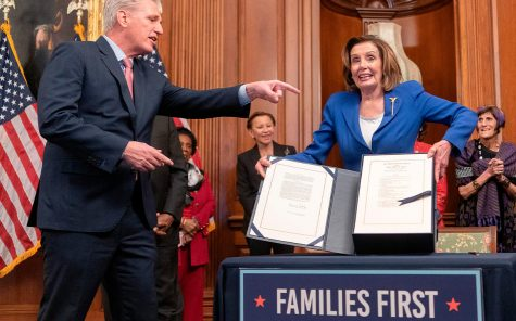 Nancy Pelosi holds up new bill.