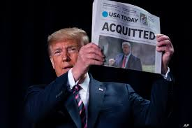 "Trump holding a newspaper, its headlines say ""ACQUITTED."""