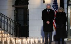 President and First Lady Biden stand on the South Portico of the White House during a candle light ceremony for those lost to COVID-19.