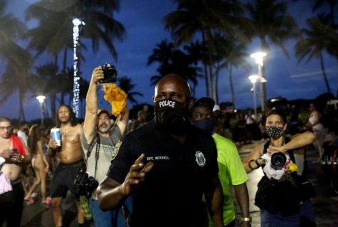 A police officer walks around Ocean Dr. reminding the crowd of the 8p.m. curfew imposed by local authorities at South Beach during Spring Break in Miami, March 27, 2021.