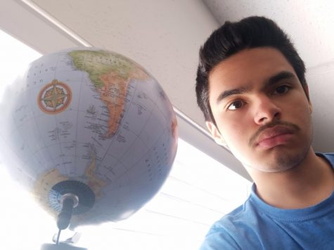 Daniel to the right of a globe displaying South America because hes too short for us to see North America.